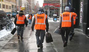 NY Dept of Sanitation workers on the street in orange vests with DSNY logos