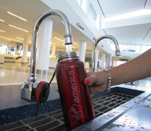 Virgin America branded water bottle getting filled at faucet